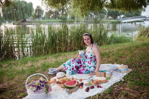 짧은 머리를 가진 긴 드레스를 입은 소녀는 과일과 패스트리가있는 흰색 담요, 꽃이 든 흰색 바구니에 앉아 있습니다.