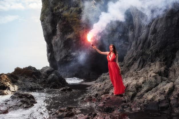長い赤いドレスを着て、手にトーチを持った少女が海の岩の多い海岸に沿って歩く