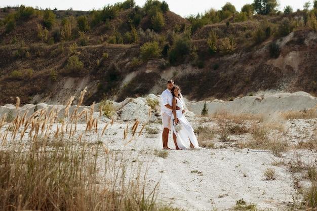Девушка в длинном белом платье с цветами в волосах и мужчина в белой рубашке и шортах на фоне белого пляжного песка и сухой травы