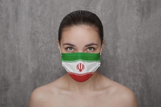 이란 국기와 함께 얼굴에 마스크를 쓴 소녀