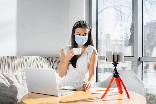 マスクをした女の子がオフィスに座ってビデオブログを撮影しています。