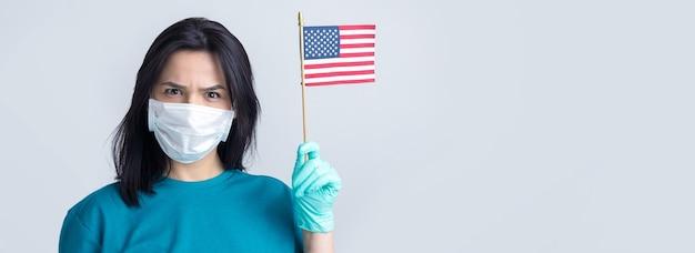 医療用マスクと手袋をはめた少女が手にアメリカ国旗を持っているコロナウイルスの概念