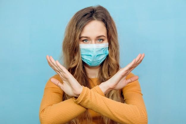 腕を組んでサインを示す青色の背景に医療用マスクの女の子がいなくなっています。概念的なソーシャルポスターは、covid-19ウイルスの拡散を遅らせるのに役立ちます。パンデミックを止めましょう。