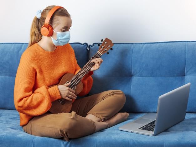 의료 마스크를 쓴 소녀가 노트북에서 우쿨렐레를 연주합니다.