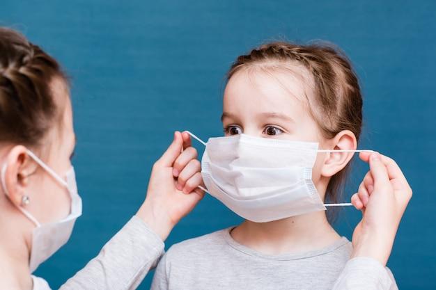 医療用マスクの女の子が別の女の子にきれいなマスクをかけます。児童保護