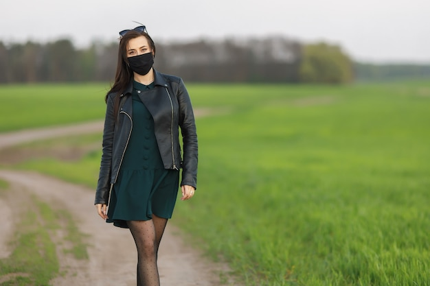 Девушка в медицинской маске бежит или идет по зеленому полю. карантин весна-лето. коронавирус.