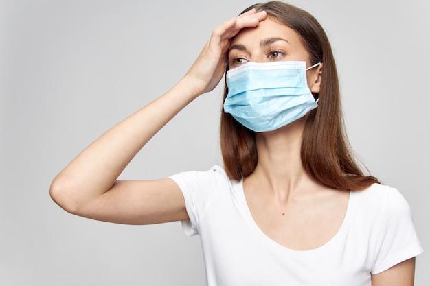 Девушка в медицинской маске касается головы руками проблемы со здоровьем высокая температура перед дуэлью