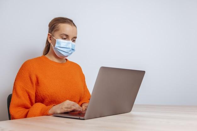 Девушка в медицинской маске работает за ноутбуком