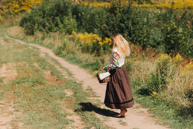Девушка в национальном костюме с корзиной цветов гуляет по зеленому полю национальный костюм