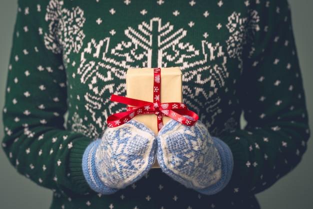 新年のセーターを着た女の子がプレゼントを持っています。男性への贈り物。メリークリスマス。女の子への贈り物。クリスマスの飾りとセーター。ニットドレス。