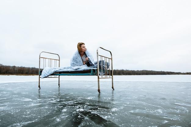 凍った青い湖のベッドで目を覚ますナイトガウンと毛布の女の子