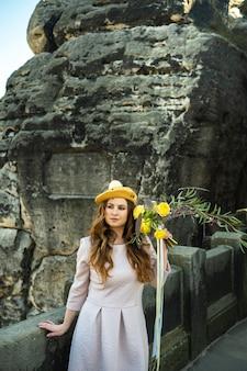 ピンクのドレスと帽子をかぶった少女が、ドイツのスイスザクセン州バスタイの山と峡谷の表面に花束を持っています。