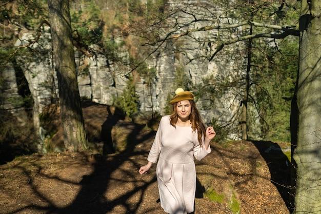 Девушка в розовом платье и шляпе на фоне гор и ущелий в швейцарской саксонии, германии, бастай.