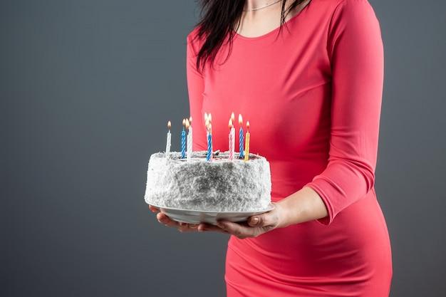 ピンクのドレスを着た少女は、彼女の手で燃えるろうそく、クローズアップでケーキを保持しています。お誕生日おめでとうお祝いお祝いパーティー記念日。コピースペース。