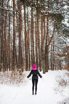 분홍색 스카프와 모자를 입은 소녀가 소나무 숲 한가운데 서 있습니다. 서리가 내린 날에 아름다운 소나무 숲.