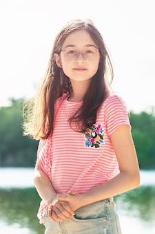 夏の川辺でピンクの縞模様のtシャツとデニムのスカートをはいた女の子。自然の中の 10 代の少女。