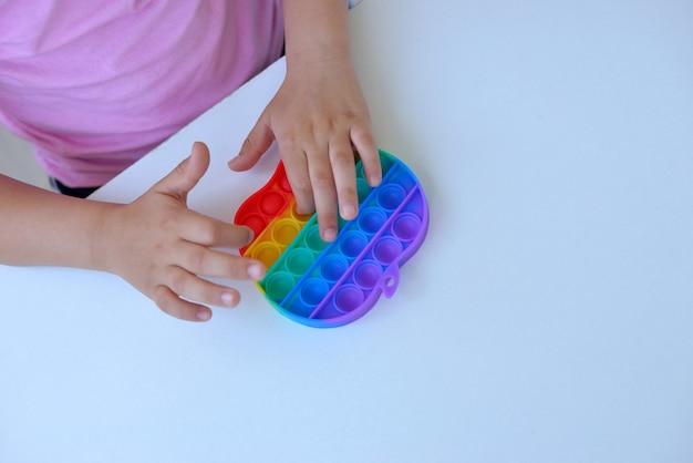 Девушка в розовой футболке играет с модной игрушкой. красочная антистрессовая сенсорная игрушка непоседа толчок поп ее в руки ребенка, может использоваться для тренировок с аутичными людьми.