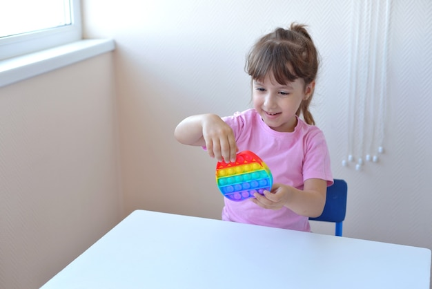ピンクのtシャツを着た女の子が流行のおもちゃで遊んでいます。カラフルな抗ストレス感覚おもちゃのそわそわは、子供の手にそれをプッシュポップし、自閉症の人々とのトレーニングに使用することができます。