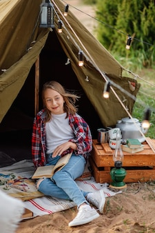 Девушка в клетчатой рубашке и синих джинсах читает книгу рядом с палаткой.