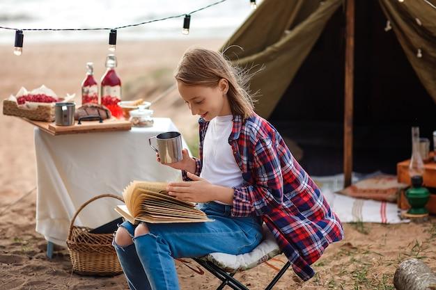 Девушка в клетчатой рубашке читает книгу на фоне палатки и озера.