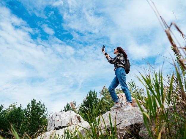 체크 무늬 셔츠를 입은 소녀가 휴대폰이나 인터넷 연결을 잡으려고하거나 셀카를 찍습니다.