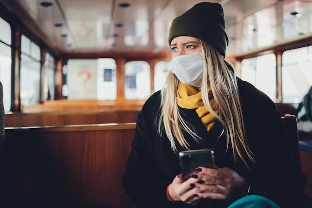 携帯電話を手にした地下鉄の車の保護マスクをかぶった少女