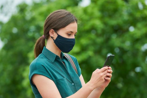 코로나 바이러스의 확산을 피하기 위해 사회적 거리를 유지하는 보호 마스크의 소녀
