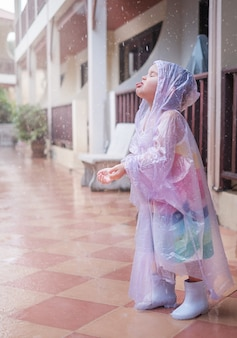 빗 속에서 비옷을 입은 소녀. 아이가 손과 혀로 빗방울을 잡습니다.