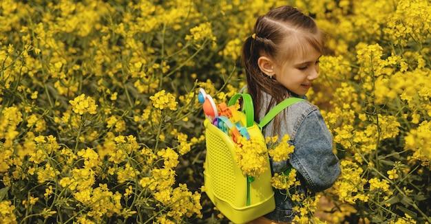 Девушка на рапсовом поле с рюкзаком, наполненным современным развивающим попитом и простыми игрушками с ямочками