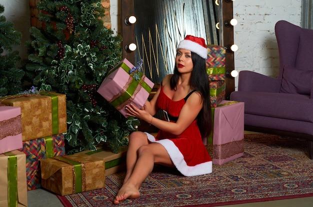 그녀의 손에 선물 빨간 크리스마스 의상 소녀.