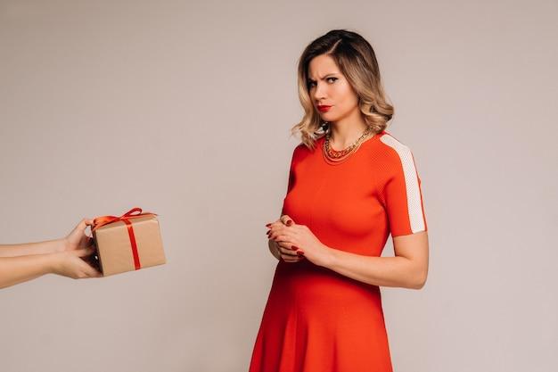 Девушка в красном платье получает подарок в руки на сером фоне