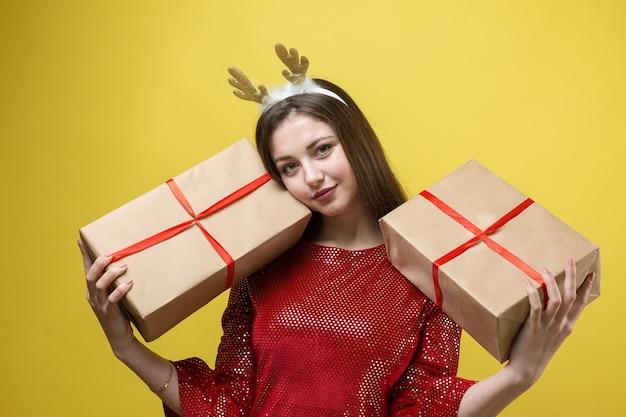 노란색 배경에 선물이 있는 빨간 드레스를 입은 소녀.