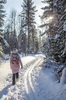빨간 재킷을 입은 소녀가 겨울 날 눈 덮인 숲을 걷는다. 배면도.