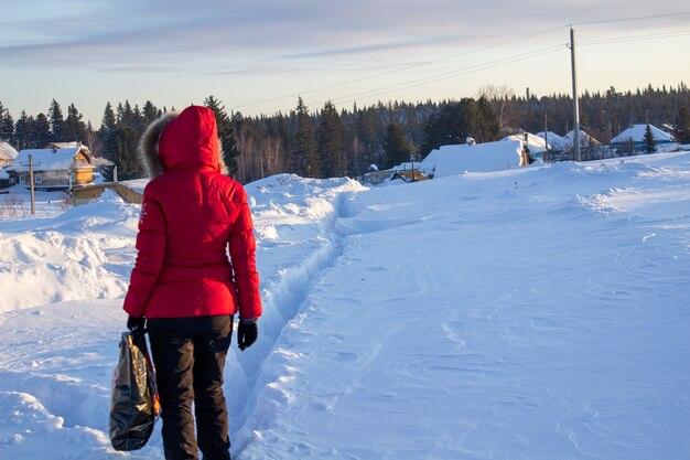 빨간 재킷을 입은 소녀가 러시아 시베리아에서 눈 더미를 걷고 있습니다.