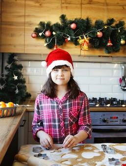 赤いシャツとクリスマスの帽子をかぶった女の子が、キッチンのお祝いのクリスマステーブルにジンジャークッキーを準備しています。