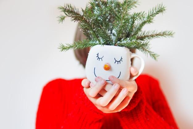 赤いセーターを着た女の子が、雪だるまの顔の前にモミの枝が付いたマグカップを持っています。