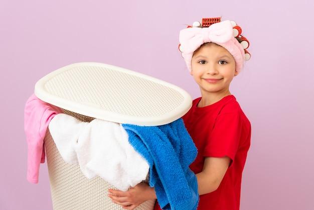 赤いtシャツを着た女の子が汚れた洗濯物のバスケットを持っています。