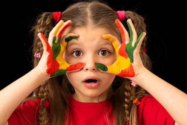 Девушка в красной футболке на черном фоне измазана краской.