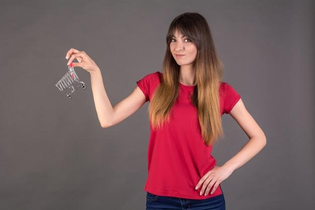 Девушка в красной футболке с тележкой для покупок