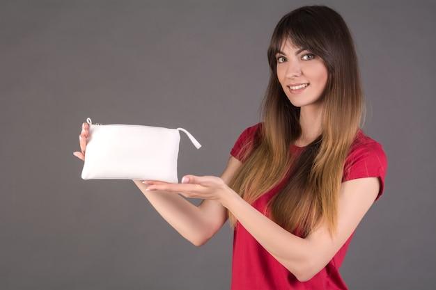 Девушка в красной футболке с белой косметичкой