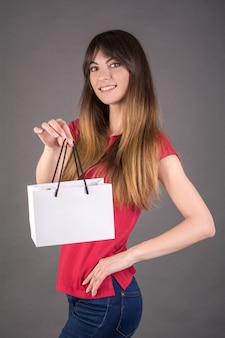 Девушка в красной футболке с белым подарочным пакетом