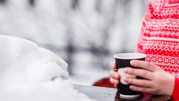 Девушка в красной теплой куртке с рисунком держит в руках стакан с горячим напитком. девушка на улице, рядом снег. фото