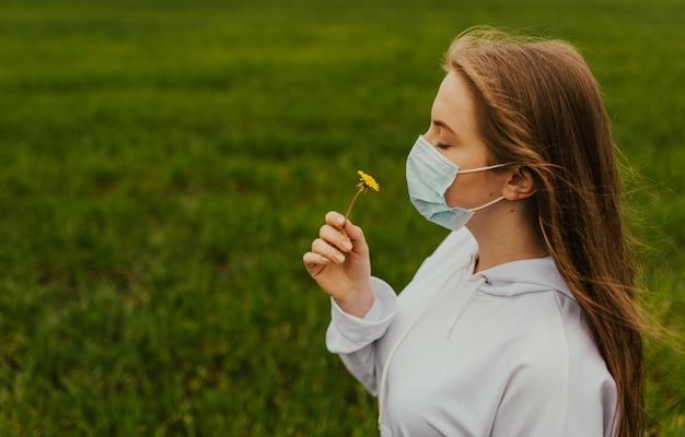 レスピレーターの女の子が黄色いタンポポを嗅ぎます。屋外の保護マスクで若い金髪のヨーロッパの女性。