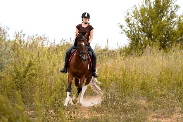 Девушка в шлеме для верховой езды скачет на пегом коне по полю среди зеленых кустов навстречу фотографу.