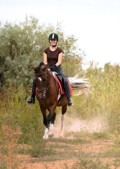 Девушка в шлеме для верховой езды едет на пегом коне рысью по полю среди зеленых кустов к фотографу.