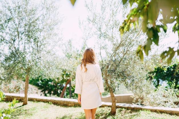 겉옷을 입은 소녀가 맑은 아침에 나무 사이 숲을 걷는다.