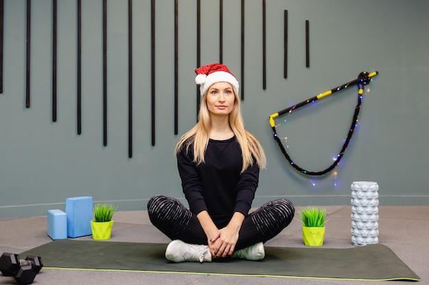 검은 색 스포츠 유니폼을 입고 체육관에서 피트니스 운동을하는 산타 클로스 모자에 소녀