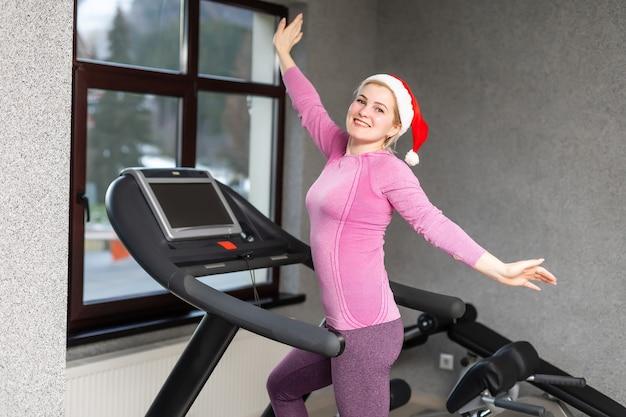 サンタクロースの帽子をかぶった女の子がジムでフィットネスエクササイズをし、スポーツユニフォームを着て、クリスマスのフィットネス活動をしています。新年。クリスマス、休日、フィットネス、ジムのコンセプト。