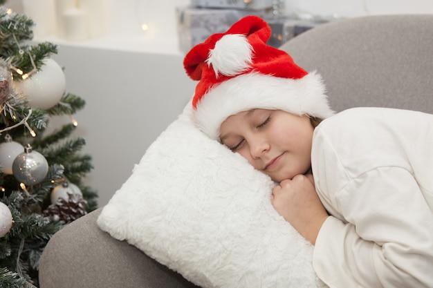 サンタクロースの帽子をかぶった女の子がソファで寝ています