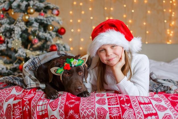 강아지와 함께 산타 클로스 모자에 소녀는 크리스마스 트리 근처 침대에 누워